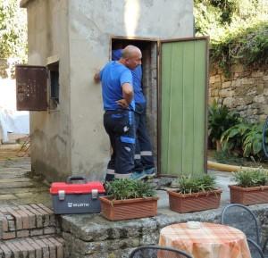 Due operai lavorando al pozzo di Isola Maggiore.
