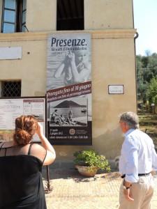 Sulla facciata del Museo del Merletto, il manifesto della mostra fotograficadedicata al fotoreporter Enrico Valentini   -   Di spalle, a destra, il signore Italo Marri.