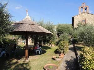 """A sinistra, il lato sud del giardino del """"Antico Orologio""""; a destra, la chiesa del Buon Gesù."""