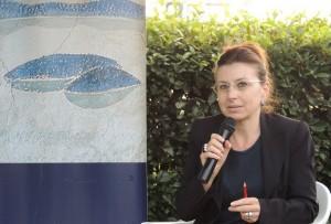 Stefania Limiti presenta il suo lavoro accanto al poster stilizzato di Isola Maggiore, Isola del Libro.