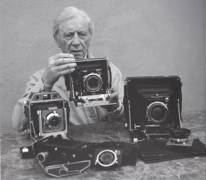 Enrico Valentini con alcune delle sue vecchie macchine fotografiche.