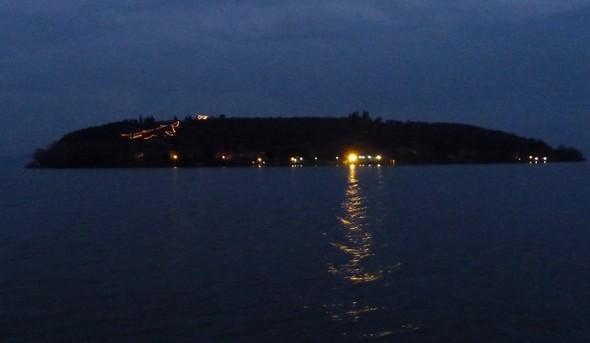 L'albero di Natale e la stella di Betlemme brillano sul lato ovest di Isola Maggiore, di fronte aTuoro sul Trasimeno.
