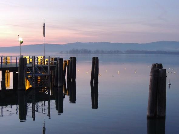 Extrémité du pontile de l'Isola Maggiore et son éclairage qui se diffuse jusqu'à un regroupement de canards - A l'arrière-plan, la Punta Navaccia - 18/12/2013,   18:16.