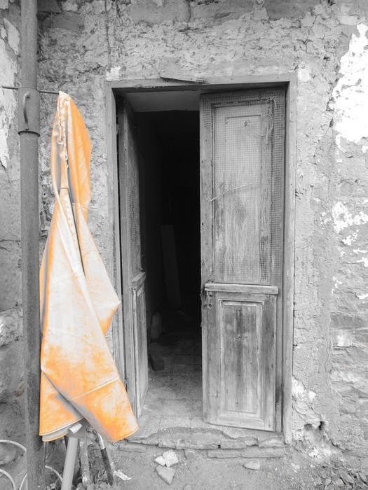 Dans la via Guglielmi, une tenue de pêcheur mise à sécher - Teinte orangée et modernité de l'habit qui tranche avec les vieilles pierres et la porte délabrée.