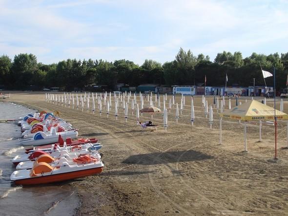 A - 113, la plage est large à souhait et les rangées de parasols sont alignées en ordre de bataille.