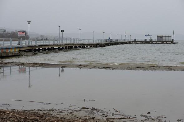 """La plage envahie par l'eau, une mince bande sable en avant-garde, ultime """"rempart"""" face au lac Trasimène, le pontile des traghetti."""
