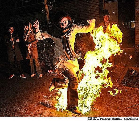 Une iranienne saute au-dessus d'un petit feu de joie à l'occasion de Chahar shanbeh suri.