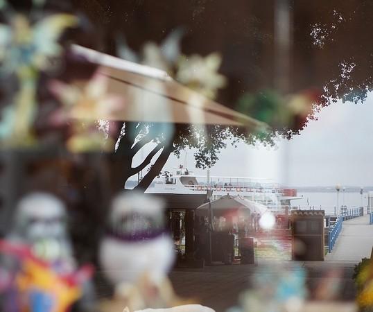 Reflet dans la vitre de La Stiva (boutique de souvenirs au fond de la piazzetta San Francesco), du départ d'un traghetto    -    3/04/2014.