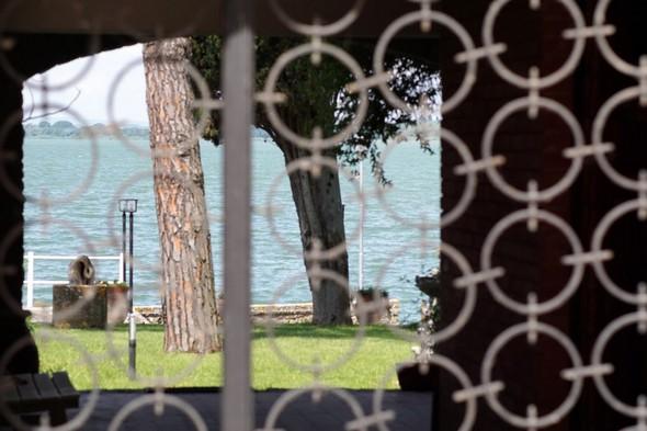 Parfois une ferronnerie plus récente clôt un ancien portique en offrant une vue ponctuelle du Trasimène...