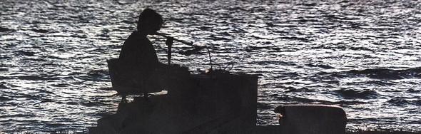 Pianiste à l'extrémité de la jetée de l'Isola Maggiore   -   foto di Riccardo Ruspi.