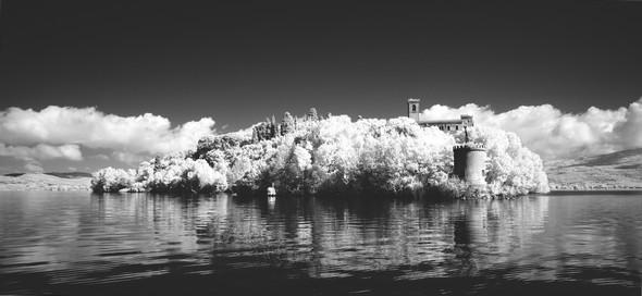 La pointe sud de l'Isola Maggiore : tout devant l'ancien moulin à vent, sur la droite, en retrait, le château Guglielmi, à l'arrière-plan à droite et à gauche, les rives du lac Trasimène du côté de Tuoro.