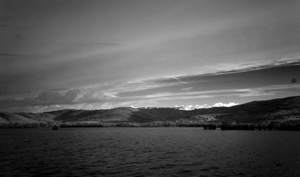 Le pontile de l'Isola Maggiore est encore dans le noir; Tutoro bénéficie lui déjà des premiers rayons de soleil; le traghetto (à gauche) navique sur un Trasimène encore bien sombre et n'est visible que grâce à ses trois feux de position.