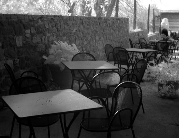 Composition centrée sur la série en diagonale des chaises sombres et leur contraste avec les zones ensoleillées.