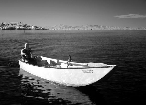 Pescatore in barca tradizionale del Lago Trasimeno.
