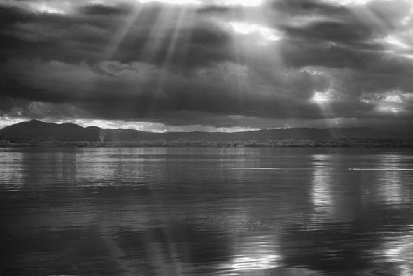 """PHOTO - La rive ouest du lac Trasimène, en face de l'Isola Maggiore et les """"coups de projecteurs"""" du soleil sur le Trasimène."""