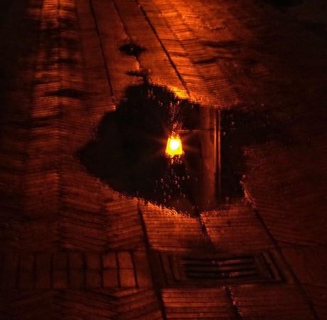 Le refletlumineux dans les flaques de pluie accentue l'étrangeté diffuse de cette atmosphère hermétique...