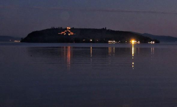 Vista dalla riva di Tuoro.  L'Isola Maggiore con l'albero di Natale illuminato e la stella brillante. 19 dicembre 2011.