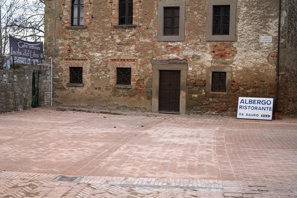 L'unico tratto di pavimentazione, che è stato ricostruito.  Allo sfondo, la casa del vescovado.