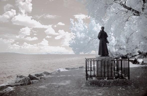 Traitement visant à évoquer l'aura surnaturelle qui nimbe saint François.Lieu du débarquement de saint François à l'Isola Maggiore en 1211.