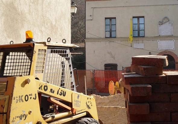 Uno dei accessi alla piazza di san Francesco è bloccato da un macchina di sterro e da un stock di sabbia e di mattone.