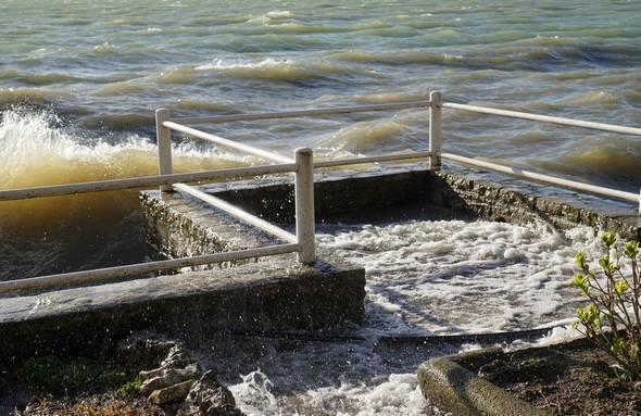 Les vagues, poussées par le Ponant, se jettent à l'assaut de la digue du jardin.