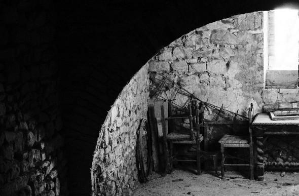 """Par une fenêtre, aperçu d'une cave voûtée et de son """"bric-à-brac"""". © Dinu Wilmotte."""