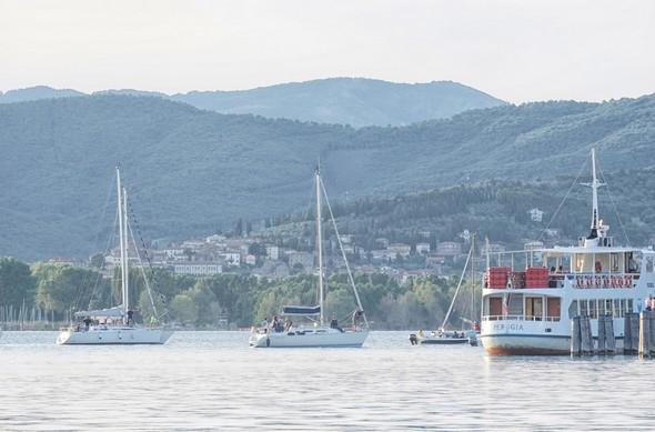 19:11Une flottille de voiliers et autres esquifs commence à se rassembler en face des deux darses et du débarcadère de l'Isola Maggiore.