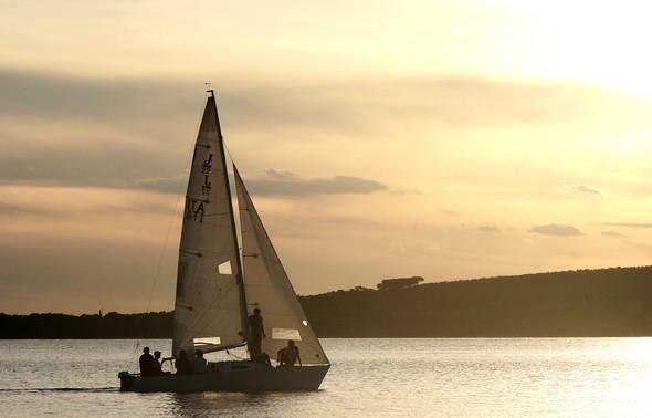 19;16.Un voilier approche.Au fond la silhouette plus sombre de la Punta Navaccia (ouest).Belle et chaude couleur orangée.