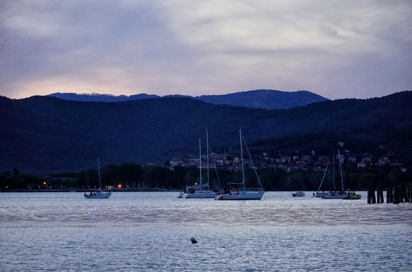 19:59En direction du nord.Les voiliers attendent le début du spectacle face à l'Isola Maggiore, à côté de son débarcadère.Le bleu profond s'apprêt à régner et l'obscurité ne va plus tarder.Au fond, Trasimeno sul Lago et ses lumières.