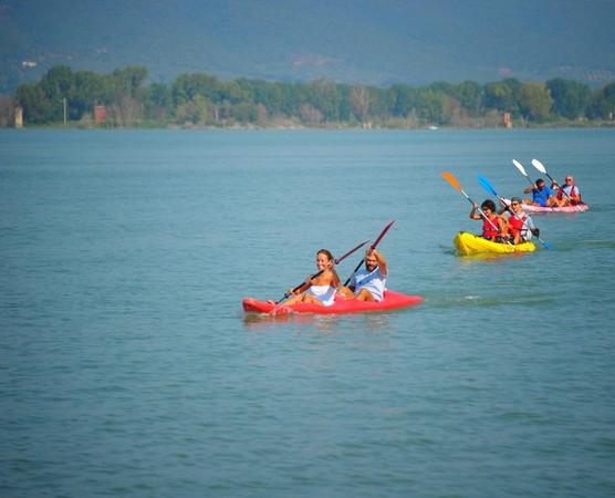 Couleurs, élégance, harmonie des gestes.Des kayaks commencent à longer la rive su-ouest de l'Isola Maggiore.En arrière-plan, la rive à hauteur de Tuoro-Navaccia. © Umberto Chiappafreddo.