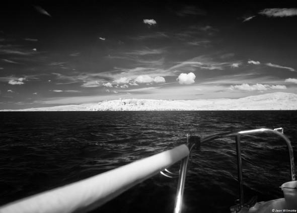 """Vue de la poupe.Sur la ligne d'horizon, à gauche, l'Isola Maggiore et la silhouette du château Guglielmi.à droite la forme plus """"grossière"""" de l'Isola Minore.Au-dessus, ce beau ciel avec quelques nuages bien solitaires...10:14."""