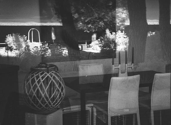 Tournant le dos au lac et au jardin, photographie de la baie vitrée de la salle à manger.Reflets du jardin et du lac décorent virtuellement la pièce.4 août 2015   -   06:16.