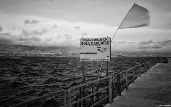 """Le point d'amarrage du """"bateau-taxi"""" pour l'Isola Maggiore.Signore Maurizio : 335-561.94.09.Action violente du vent sur le drapeau !"""