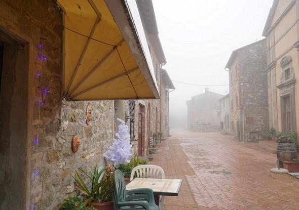 """Plus en avant en direction du nord.A gauche, l'entrée des cuisine du restaurant """"Anticho Orologio"""" avec une des deux seules décorations de Noël de la rue.Au premier plan sur la droite, l'entrée de l'église du Buon Gesù."""