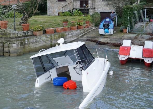 La barque se rapproche encore un peu plus de la rampe d'accès en se redressant encore.