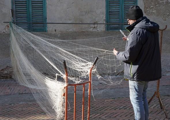 Via Guglielmi, Edoardo Silvi reprise les mailles d'un filet de pêche.