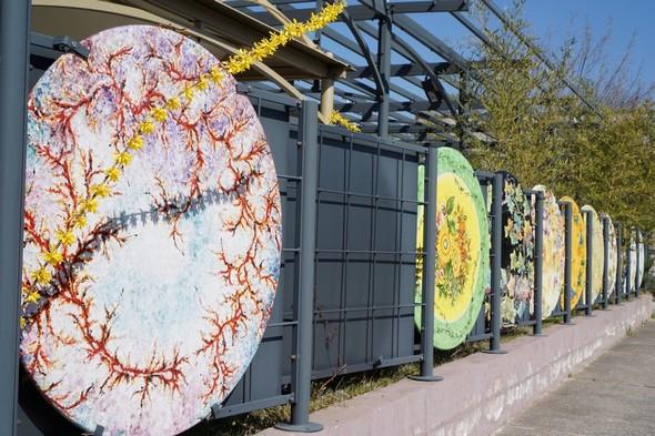 Les grilles qui entourent les grands magasins sont ornées de plateaux de table en céramique peinte.Magasins au pied de la ville, le long de la E45.Deruta.