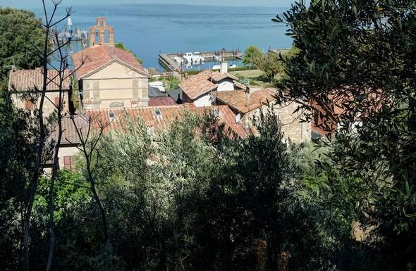A travers une trouée, vue de l'arrière de la via Guglielmi depuis la strada di San Salvatore.Quadrant supérieur gauche : la façade avant de la chiesa del Buon Gesù et son clocher.