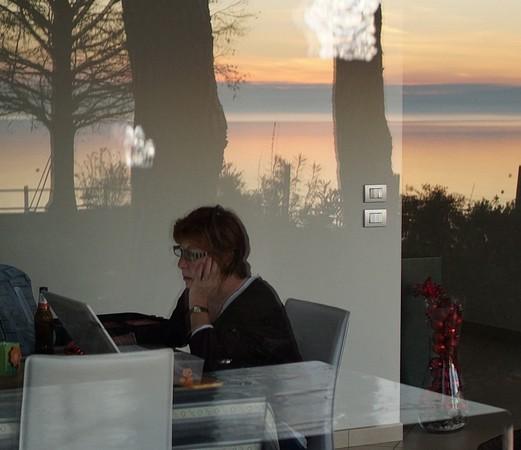 Fabienne travaille dans lle décor surréaliste de notre salle à manger noyée dans le reflet du coucher de soleil.