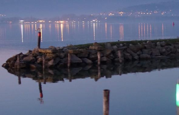 Digue de la deuxième darse de l'Isola Maggiore.Les feux rouge (babord) et vert (tribord) de son entrée.Au fond, la rive nord du lac Trasimène avec les lumières de Tuoro-sul-Trasimeno.