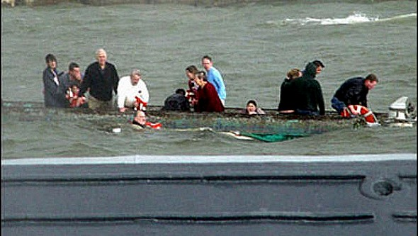 I passeggeri sopravviventi si rifugiano sullo scafo della barca-pontone rovesciata mentre una nave della US Navy arriva al loro soccorso.<br />  AP/US NAVY, Jerry Neblett.
