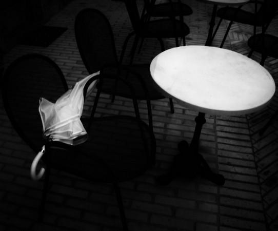 Image quasi irréaliste obtenue par renforcement des contrastes en post-production.Un parapluie abandonné sur une chaise de la terrasse du bar de Silvia.
