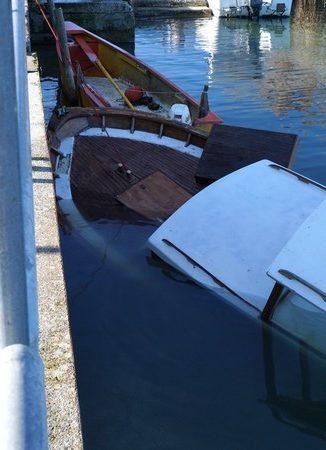 La prua della barca in legno emerge ancora. E è parzialmente incastrata sotto il cemento della lastra dello pontile.