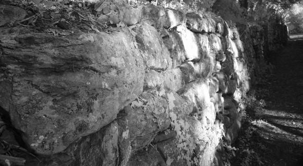 Massif mur de soutènement qui longe la via Tre Martiri, du côté menant au sommet.