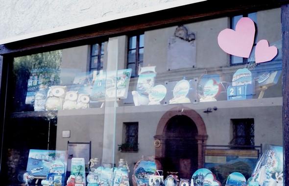 Vetrina posteriore del negozio di regali, La Stiva.Facciata del Museo del Merletto (riflesso).
