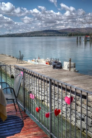 """Dal giardino del ristorante """"L'OSO"""", una vista sul suo pontile privato.Sullo sfondo, la riva nord del lago Trasimeno, vicino a Tuoro-Navaccia."""