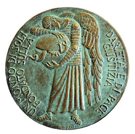 Médaillon de l'Ange de la Paix.<br />Bronze de l'artiste italien Guido Veroi (1926-2013<br />Diamètre : une vingtaine de centimètres.<br />Inscription « Un monde de solidarité et de paix fondé sur la justice ».<br />Un ange à cotte de mailles, embrassant et réunissant l'hémisphère nord et l'hémisphère sud, malgré le dragon, symbole du mal, qui s'oppose à lui.