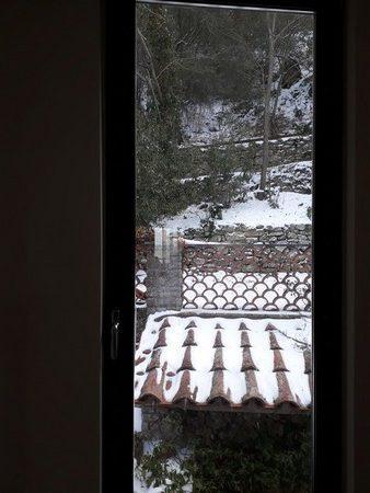 Coup d'oeil depuis notre cage d'escalier.Encore de la neige sur les tuiles, le sentier et le versant de la colline derrière la maison.