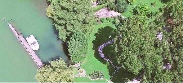 La darse et le hors-bord.Vue aérienne (drone) d'une partie du jardin (faîte des pins parasols).